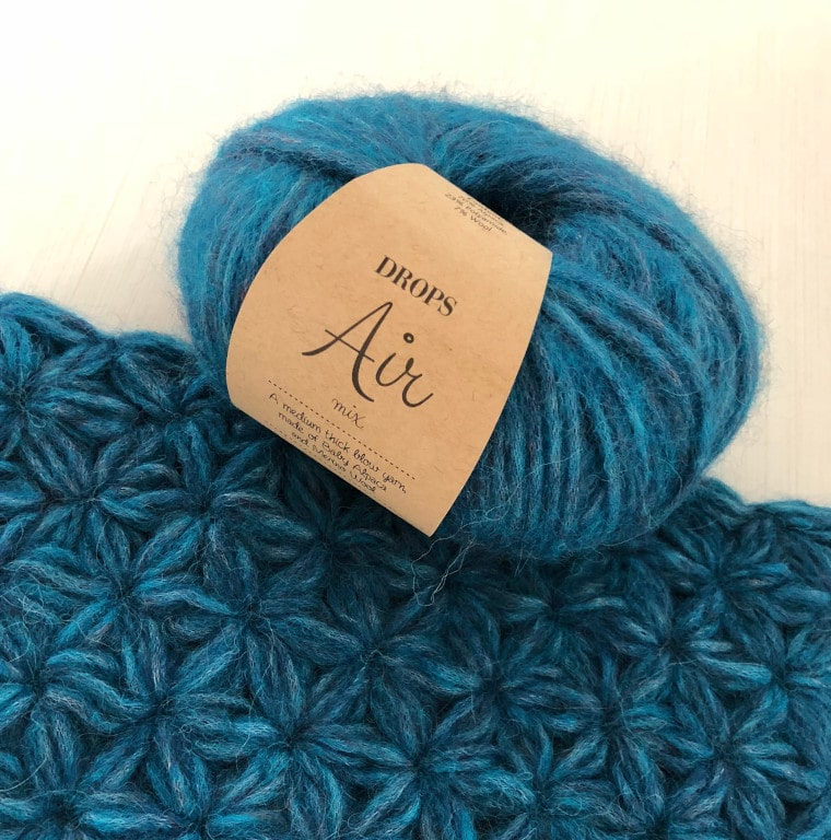 A ball of yarn of Drops Air brand and crochet jasmine stitch fabric.
