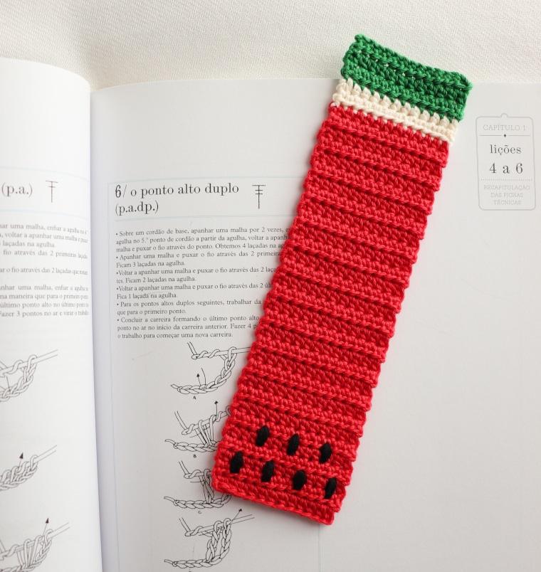 The Watermelon Bookmark of the Crochet Tropical Bookmark Set on a book